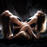 Twee aantrekkelijke mooie sexy toont spel dansende uitvoerders jonge vrouwen verleidelijke meisjesvrienden in een bodysuit zittin Stock Foto
