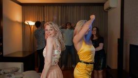 Twee aantrekkelijke sexy meisjes die bij partij met erachter vrienden dansen stock videobeelden