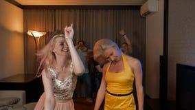 Twee aantrekkelijke sexy meisjes die bij partij met haar erachter vrienden dansen stock footage