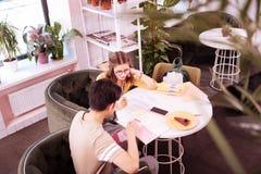 Twee aantrekkelijke studenten die voor definitief examen in koffie voorbereidingen treffen royalty-vrije stock foto's