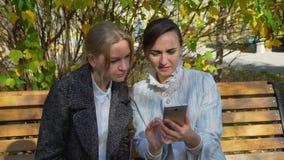 Twee aantrekkelijke vrouw het letten op foto's op smartphone stock videobeelden