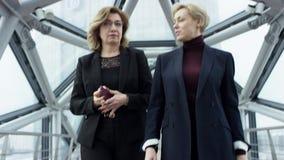 Twee aantrekkelijke vrouwelijke onderneemsters lopen en bespreken Zaken Zij allen werken in Centrale Zaken stock footage