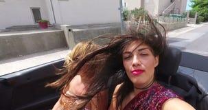 Twee aantrekkelijke vrouwen die snel in convertibel op kustweg berijden stock video