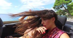 Twee aantrekkelijke vrouwen die snel in convertibel op kustweg berijden stock footage