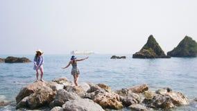 Twee aantrekkelijke vrouwengang op grote stenen door het overzees stock video