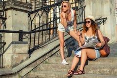 Twee aantrekkelijke vrouwentoeristen wijzen op de plaats Het concept van de vakantie De vakantie van de zomer Stock Foto's