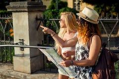 Twee aantrekkelijke vrouwentoeristen wijzen op de plaats Het concept van de vakantie De vakantie van de zomer Royalty-vrije Stock Foto