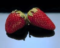 Twee aardbeien met zwarte bezinning. Stock Foto