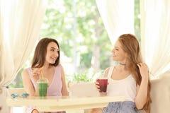 Twee aardige jonge dames die smoothie drinken royalty-vrije stock foto's