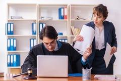 Twee advocaten die in het bureau werken stock foto