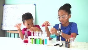 Twee Afrikaanse Amerikaanse gemengde jonge geitjes die het experiment van het chemielaboratorium testen stock video