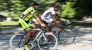 Twee Afrikaanse Amerikaanse mensen die weg het rennen fietsen berijden stock afbeeldingen