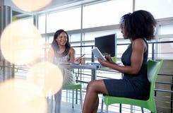 Twee Afrikaanse Amerikaanse vrouwen die ideeën bespreken die een tablet en een computer met behulp van Royalty-vrije Stock Foto's