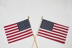 Twee Amerikaanse vlaggen die elkaar op witte achtergrond kruisen royalty-vrije stock afbeelding