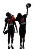 Twee Amerikaanse voetbalsters die achtermeningssilhouet lopen stock afbeeldingen