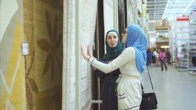 Twee Arabische jonge vrouwen in hijab kiezen tapijt stock videobeelden