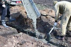 Twee arbeider-bouwers vullen het concrete bestaan uit cement en s in royalty-vrije stock foto