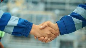 Twee arbeiders bij de bouwwerf het geven van handschok Industriële Achtergrond Close-up stock video