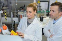 Twee arbeiders bij productielijn in geavanceerd technisch planten royalty-vrije stock afbeelding