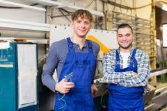 Twee arbeiders die aan een machine werken royalty-vrije stock foto's