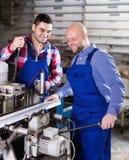 Twee arbeiders die aan machine werken Royalty-vrije Stock Foto