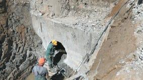 Twee arbeiders die de bouwcollector herstellen stock videobeelden