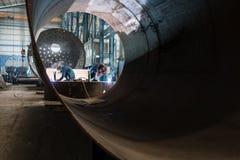 Twee arbeiders die in een fabriek productieboilers lassen stock foto
