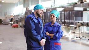 Twee arbeiders die in fabriek spreken stock footage