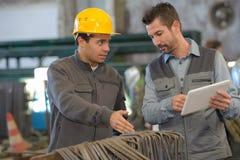 Twee arbeiders die in fabriek werken stock afbeeldingen