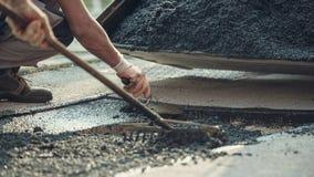 Twee arbeiders die nieuw asfalt leggen royalty-vrije stock foto