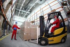 Twee arbeiders die pallets met vorkheftrucktru herladen Royalty-vrije Stock Foto's