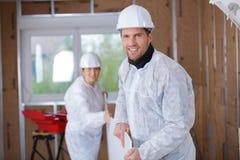 Twee arbeiders die plank dragen bij bouwwerf stock fotografie
