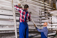 Twee arbeiders die pvc-vensterprofiel kiezen stock fotografie