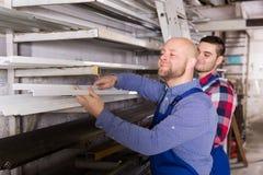 Twee arbeiders die pvc-vensterprofiel kiezen royalty-vrije stock fotografie