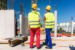 Twee arbeiders die veiligheidsmateriaal dragen terwijl het planning van het werk stock foto