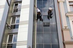 Twee Arbeiders die vensters bij de hoge stijgingsbouw schoonmaken Stock Foto
