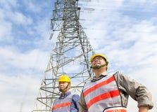 Twee arbeiders die zich vóór elektromachtstoren bevinden Stock Afbeeldingen
