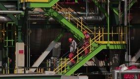 Twee arbeiders gaan onderaan treden van een raffinaderijtoren stock footage