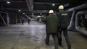 Twee arbeiders gaan op fabriek Ingenieurs in productiezaal stock footage