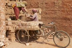 Twee arbeiders laden fiets met bakstenen in Dhaka, Bangladesh Royalty-vrije Stock Foto's