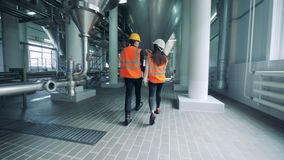 Twee arbeiders lopen langs de brouwerijeenheid stock video