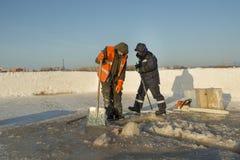 Twee arbeiders in overall verwijderen ijs uit het gat stock foto