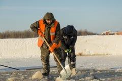 Twee arbeiders in overall verwijderen ijs uit het gat stock afbeelding