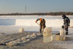 Twee arbeiders in overall verwijderen ijs uit het gat royalty-vrije stock afbeelding