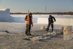 Twee arbeiders in overall verwijderen ijs uit het gat royalty-vrije stock afbeeldingen