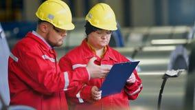 Twee arbeiders in productie-installatie als team die, industriële scène op achtergrond bespreken stock videobeelden