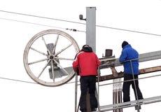 Twee arbeiders van de skilift herstellen het spinnende mechanisme van de lagere post Het reparatiewerk aangaande een de wintertoe stock afbeeldingen