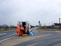 Twee arbeiders van de wegdienst kwamen aan hun officiële auto werken om gebroken verkeersteken op de weg te herstellen Het repara stock fotografie