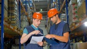 Twee arbeiders vergelijken gegevens bij een pakhuis stock videobeelden