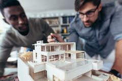 Twee architecten die architecturaal model in bureau maken stock foto